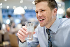 Smiling young man drinking water in cafe Stock Image
