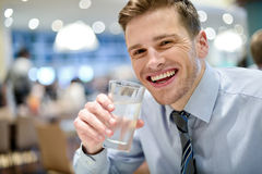 Smiling young man drinking water in restaurant Stock Images