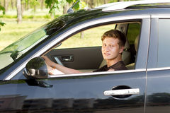 Smiling young man driving a car. View through the open side window of a smiling handsome young man driving a car in countryside Stock Photos
