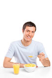 Smiling young man eating cornflakes at breakfast. A smiling young man eating cornflakes at breakfast isolated on white background Royalty Free Stock Photography