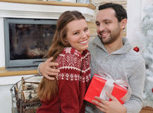 Smiling young man embraces his girlfriend and giving her Christm Royalty Free Stock Image