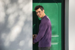 Smiling young man entering a door. Smiling young man entering a green door in an exterior wall of a house turning to look at the camera with a friendly smile Royalty Free Stock Image