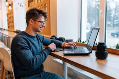 Cheerful man sitting at cafe and working on laptop Stock Image