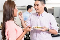 Man feeding food to her girlfriend. Smiling young men feeding food to her girlfriend in the party royalty free stock photography