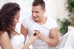 A smiling young man gives a girl a gift Stock Images
