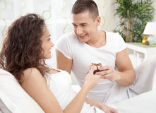 A smiling young man gives a girl a gift Royalty Free Stock Photography