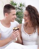 A smiling young man gives a girl a gift Royalty Free Stock Photos