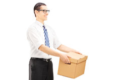 Smiling young man giving a box to someone Royalty Free Stock Photo