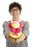Smiling young man giving flower. Smiling asian young man giving congratulation toy flower, isolated Royalty Free Stock Images