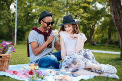 Smiling young man giving flower to his girlfriend on picnic Stock Photography
