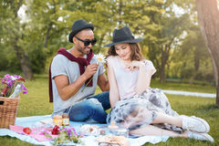 Smiling young man giving flower to his girlfriend on picnic Stock Image