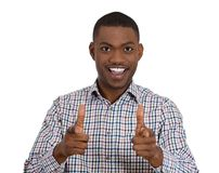 Smiling young man giving two gun sign at the camera Royalty Free Stock Photography