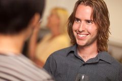 Smiling Young Man with Glass of Wine Socializing. In a Party Setting Royalty Free Stock Photos