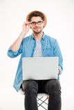 Smiling young man in glasses and hat using laptop Royalty Free Stock Photography