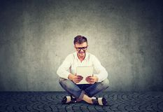 Smiling young man in glasses using a tablet sitting relaxed on a floor royalty free stock images