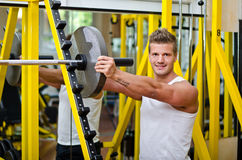 Smiling young man in gym putting weight disc on barbell Stock Images