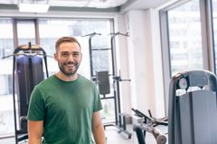 Smiling man surrounded by gym equipment. Stock Image