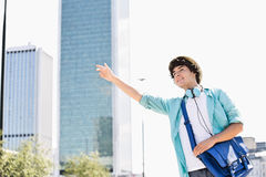 Smiling young man hailing a taxi in city Stock Photos