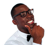 Smiling young man with hand on chin Stock Images