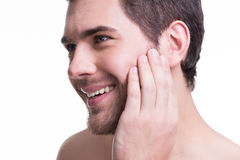 Smiling young man with hand near the face. Stock Photos