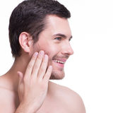 Smiling young man with hand near the face. Royalty Free Stock Photos