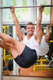 Smiling young man hanging from gym equipment Stock Photo