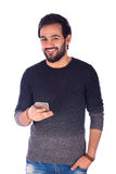 Smiling young man. Happy handsome beard young man smiling and holding a smartphone, guy wearing gray t-shirt, isolated on white background Stock Images
