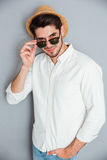 Smiling young man in hat standing and looking over sunglasses Royalty Free Stock Photos
