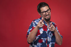 Smiling young man in Hawaiian shirt pointing towards camera. Man in Hawaiian shirt pointing at you Royalty Free Stock Images