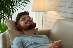 Relaxing music. Smiling young man in headphone lying on sofa and enjoying music Stock Image