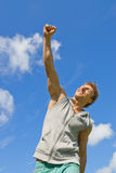 Smiling young man with his arm raised in joy. Outdoors on a sunny day Stock Photography
