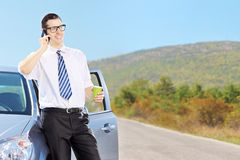 Smiling young man on his automobile talking on a phone and drink Royalty Free Stock Image