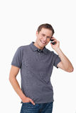 Smiling young man on his mobile phone Royalty Free Stock Images