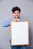 Smiling young man holding blank board Stock Images