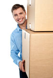 Smiling young man holding cardboard boxes Stock Photos