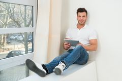 Smiling young man holding digital tablet Royalty Free Stock Photography