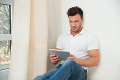 Smiling young man holding digital tablet Royalty Free Stock Photo