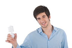 Smiling young man holding energy saving light bulb Royalty Free Stock Photos