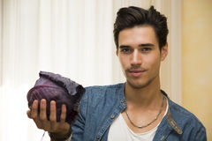 Smiling young man holding a fresh black cabbage in his hand Stock Images