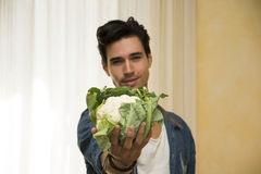 Smiling young man holding a fresh cauliflower in his hand Royalty Free Stock Photography