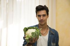 Smiling young man holding a fresh cauliflower in his hand Stock Images