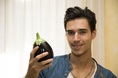 Smiling young man holding a fresh eggplant Stock Photography