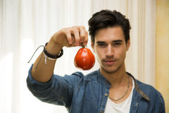 Smiling young man holding a fresh red tomato Royalty Free Stock Images