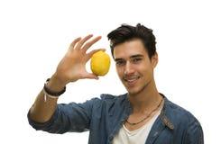 Smiling young man holding a fresh yellow lemonin his hand Royalty Free Stock Photo