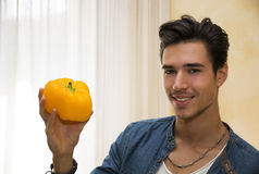 Smiling young man holding a fresh yellow pepper or capsicum in his hand Stock Images