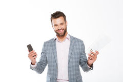 Smiling young man holding gazette and mobile phone. Royalty Free Stock Photo