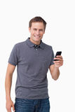 Smiling young man holding his cellphone Royalty Free Stock Photography