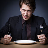 Hungry business man. Young business man holding knife and fork with empty plate on the table with dark gray background Stock Photos