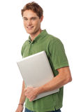 Smiling young man holding laptop Stock Image