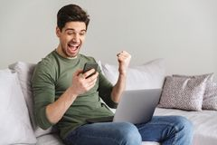 Smiling young man. Holding mobile phone while sitting on a sofa at home with laptop computer and celebrating Stock Photos